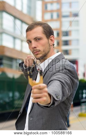 Handsome buisness man concentrated aiming a slingshot at urban city background
