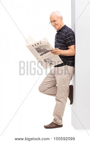 Full length profile shot of a senior gentleman reading a newspaper and leaning against a wall isolated on white background