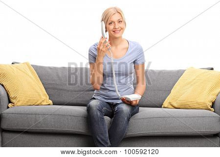 Young blond woman talking on telephone seated on a gray sofa and looking at the camera isolated on white background