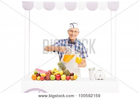 Senior soda jerk pouring orange juice into a glass and looking at the camera isolated on white background