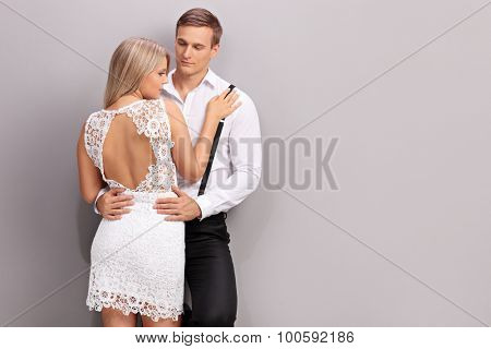 Young couple in fashionable clothes posing together against a gray wall
