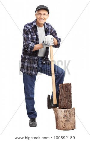 Full length portrait of a senior gentleman posing next to a small log and leaning on an axe isolated on white background
