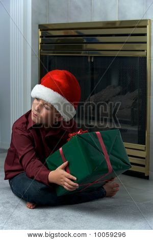 Boy In Santa Hat Shaking Gift