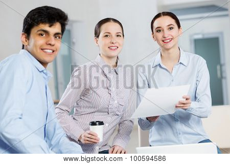 Three students working in cooperation using laptop while having coffee