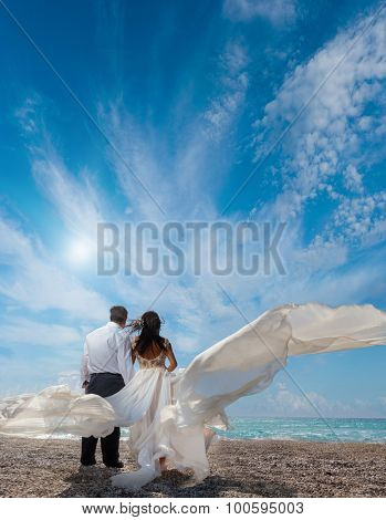 A married couple, bride and groom, together in sunshine on a beautiful tropical beach