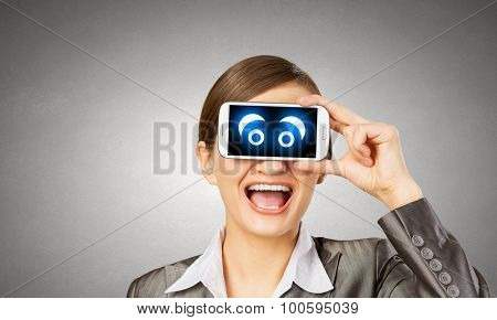 Beautiful young woman holding mobile phone against her eyes