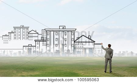 Back view of man engineer drawing plan sketches on wall