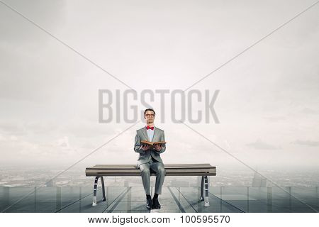Young businessman wearing red bow tie sitting on bench with book in hands
