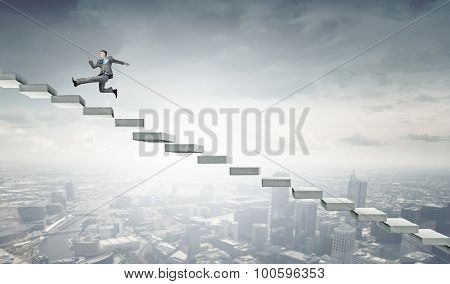 Young businessman running up on staircase representing success concept
