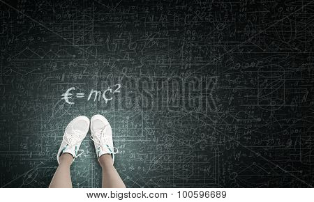 Top view of girl in sport shoes standing on blackboard