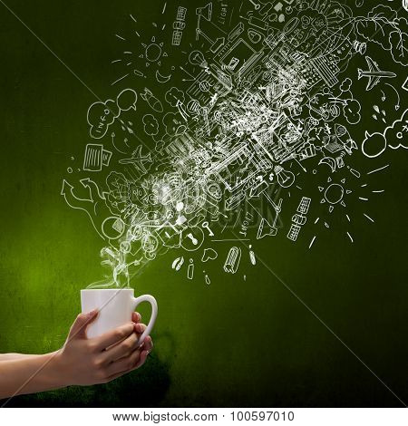 Close up of hand holding white mug of tea or coffee