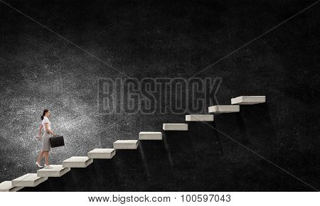Young businesswoman walking up staircase representing success concept