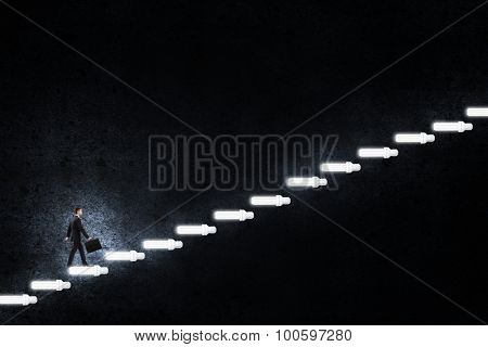 Young businessman walking up staircase representing success concept