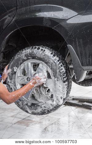 Worker Washing Car's Alloy Wheels On A Car Wash