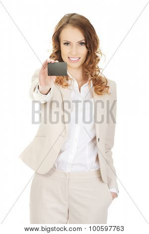 Happy businesswoman holding blank card.
