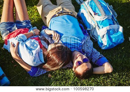 Two amorous travelers having rest on green grass