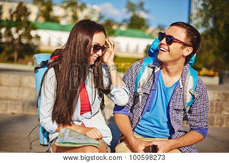 Affectionate couple of tourists interacting in urban environment