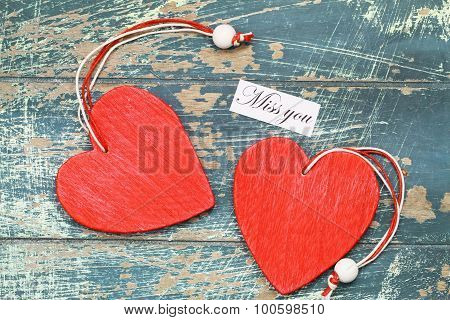 Miss you card with two red wooden hearts on rustic surface