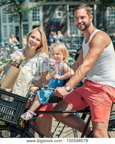 Young smiling family riding bicycles at the streets of Amsterdam