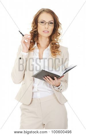 Thoughtful businesswoman holding a note.