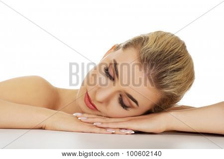Young sad woman based on table, isolated on white