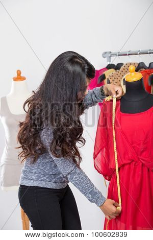 Fashion Designer Or Tailor Working On A Design Or Draft, She Takes Measure On A Dressmakers Dummy