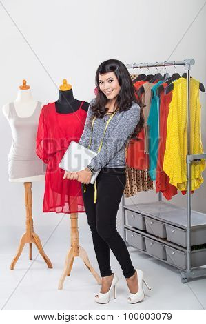 Young Asian Designer Woman Using A Tablet And Smiling,clothes Hanged As Background