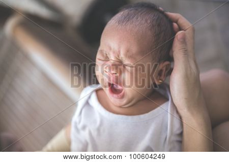 Cute Newborn Baby Carried By Her Mother While Yawning