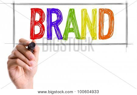Hand with marker writing the word Brand