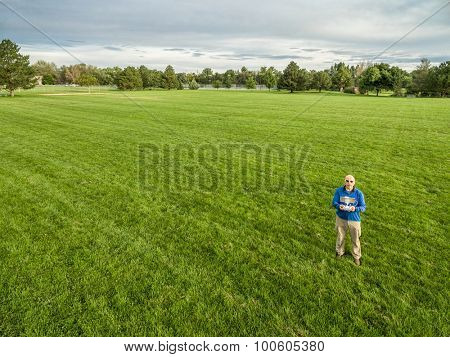 aerial shot of a male drone operator with a radio controller on a green grassy field