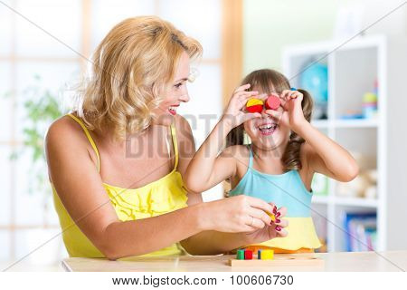 Mother and Daughter Have Fun Playing with Toys