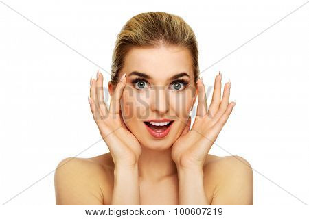A young woman checking wrinkles on her forehead, isolated on white.
