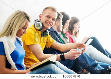 Group of students on a break reading books and using smartphones. Focus on a teenage boy. Background is blurry.
