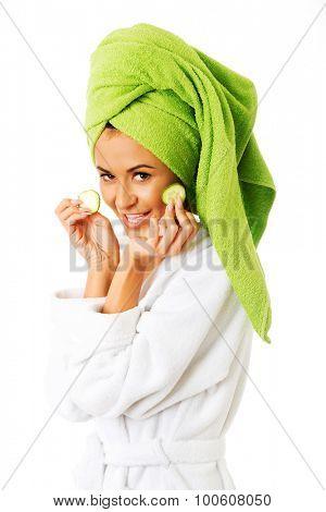 Spa woman in bathrobe applying cucumber on eyes.