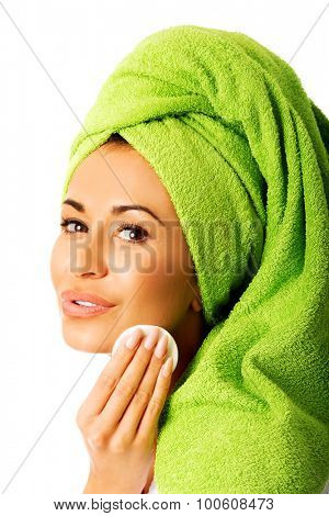 Spa woman in bathrobe removing makeup.