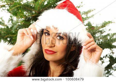 Beautiful santa woman with christmas tree on background.