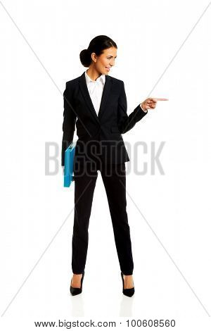 Businesswoman with binder pointing to the right.