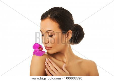 Spa woman with purple orchid petal on shoulder.