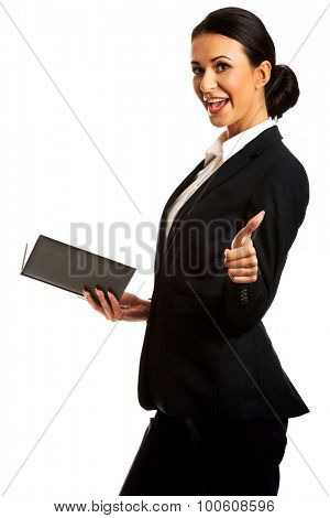 Businesswoman holding notes and showing ok sign.