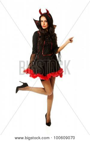 Slim woman wearing devil clothes pointing up
