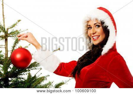 Smiling woman wearing santa claus clothes decorating christmas tree.