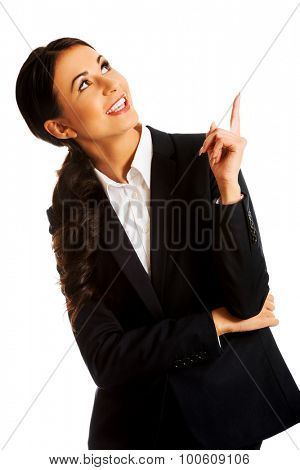Smiling businesswoman pointing up on something.