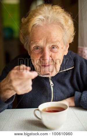 Grandma drinking tea in the kitchen.