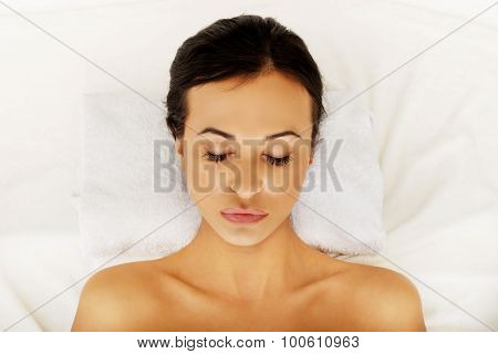 Beautiful woman relaxing in spa with closed eyes.