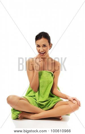 Spa woman wrapped in towel sitting cross legged.