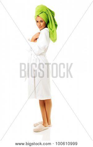 Woman standing in bathrobe wearing flippers
