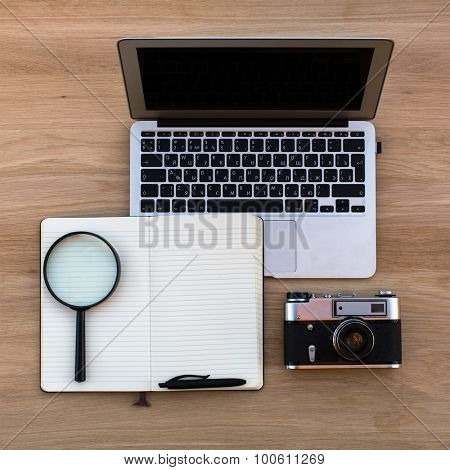 Laptop, Notepad with pen, magnifying glass and vintage camera, top view lying on texture of wood.