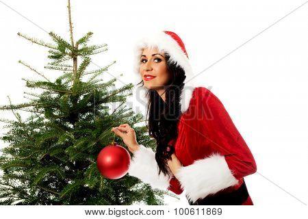 Woman wearing santa claus clothes decorating christmas tree.