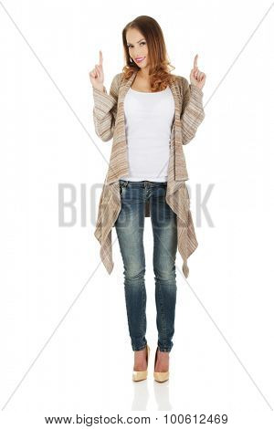 Happy smiling beautiful woman pointing up.