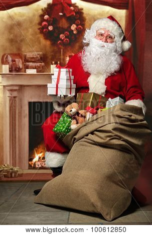 Santa Claus with a bag full of presents having a rest at the fireplace
